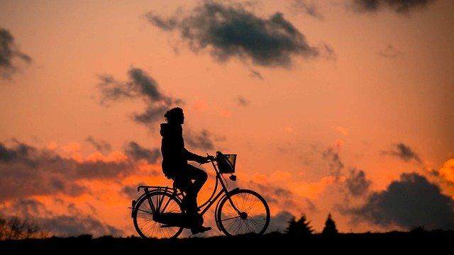 夕日の中、自転車に乗る女性