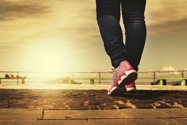 スニーカーを履いて歩く女性の後ろ姿