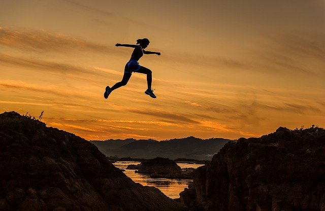 夕日の中をジャンプする女性の姿