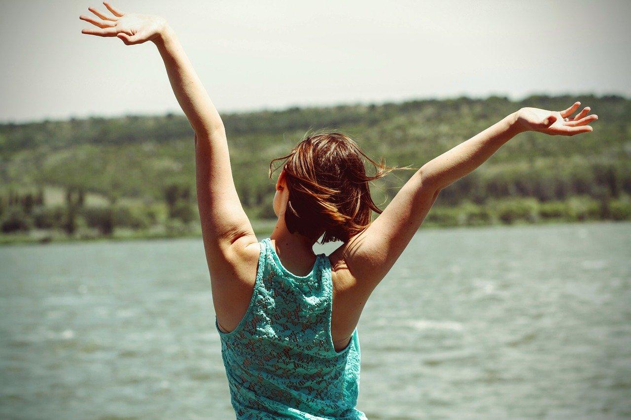 海に向かって手を広げる女性